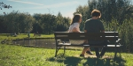 Para siedzaca na ławce wparku i rozmawiająca