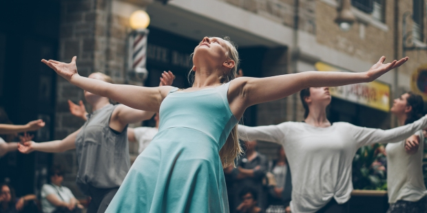 Kobieta tańcząca w grupie tancerzy na ulicy