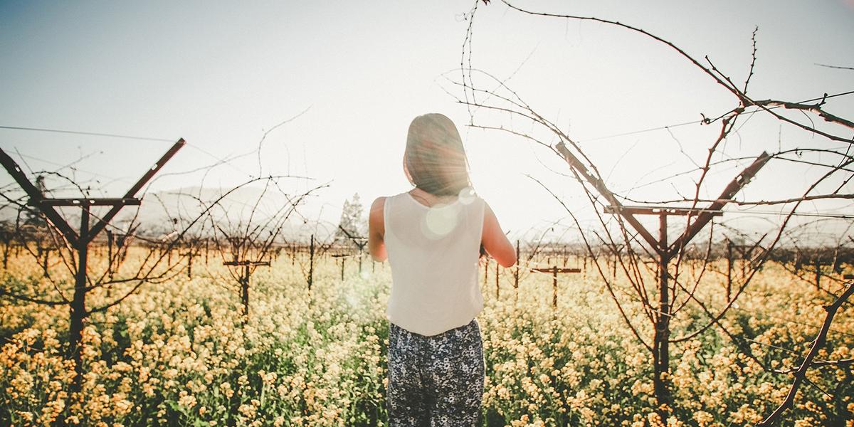 Młoda dzieczyna stoi na polu w słońcu