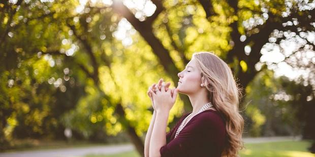 Dziewczyna modląca się w parku