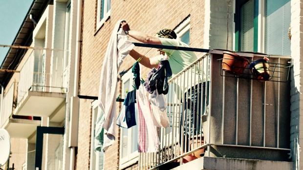 Kobieta stojąca na balkonie i wiszące pranie
