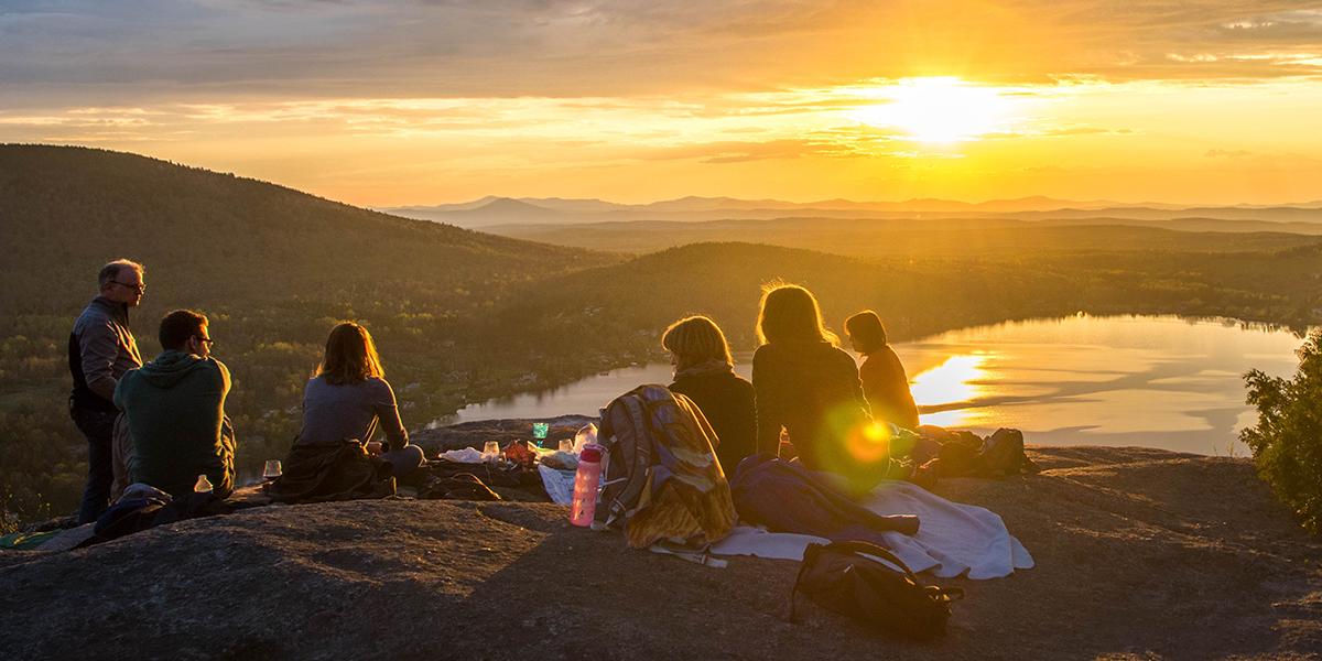 Ludzie oglądają zachód słońca w górach