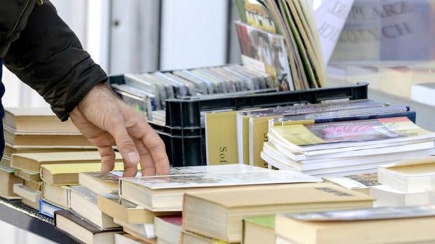 Mężczyzna przegląda książki na straganie