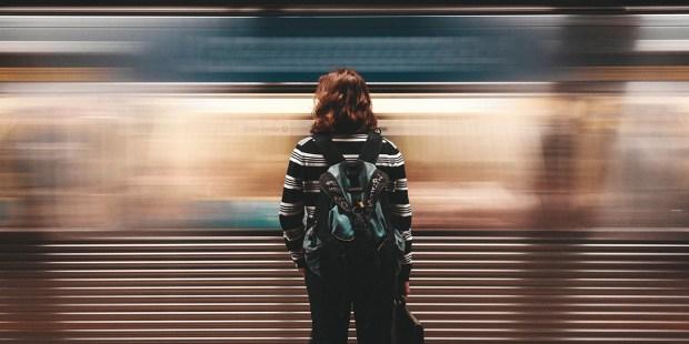 Kobieta stojąca na peronie metra przed przejeżdżającym wagonem
