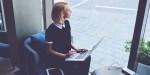 Dziewczyna z laptopem przy pracy w oknie