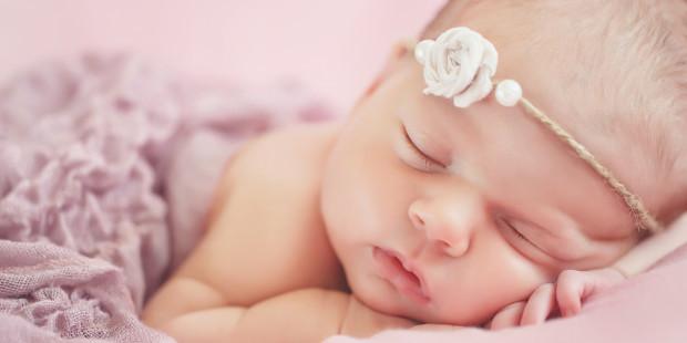 Niemowlę śpiące z opaską z kwiatkiem na głowie