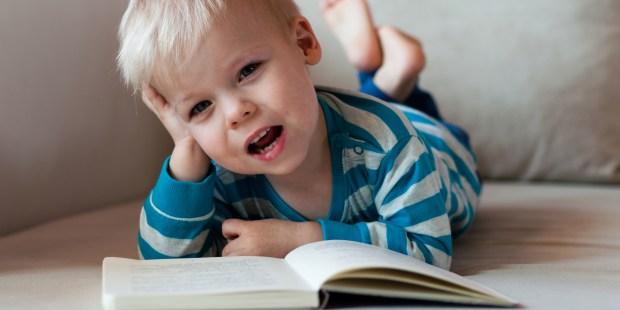 Mały chłopczyk na kanapie udaje że czyta i opowiada