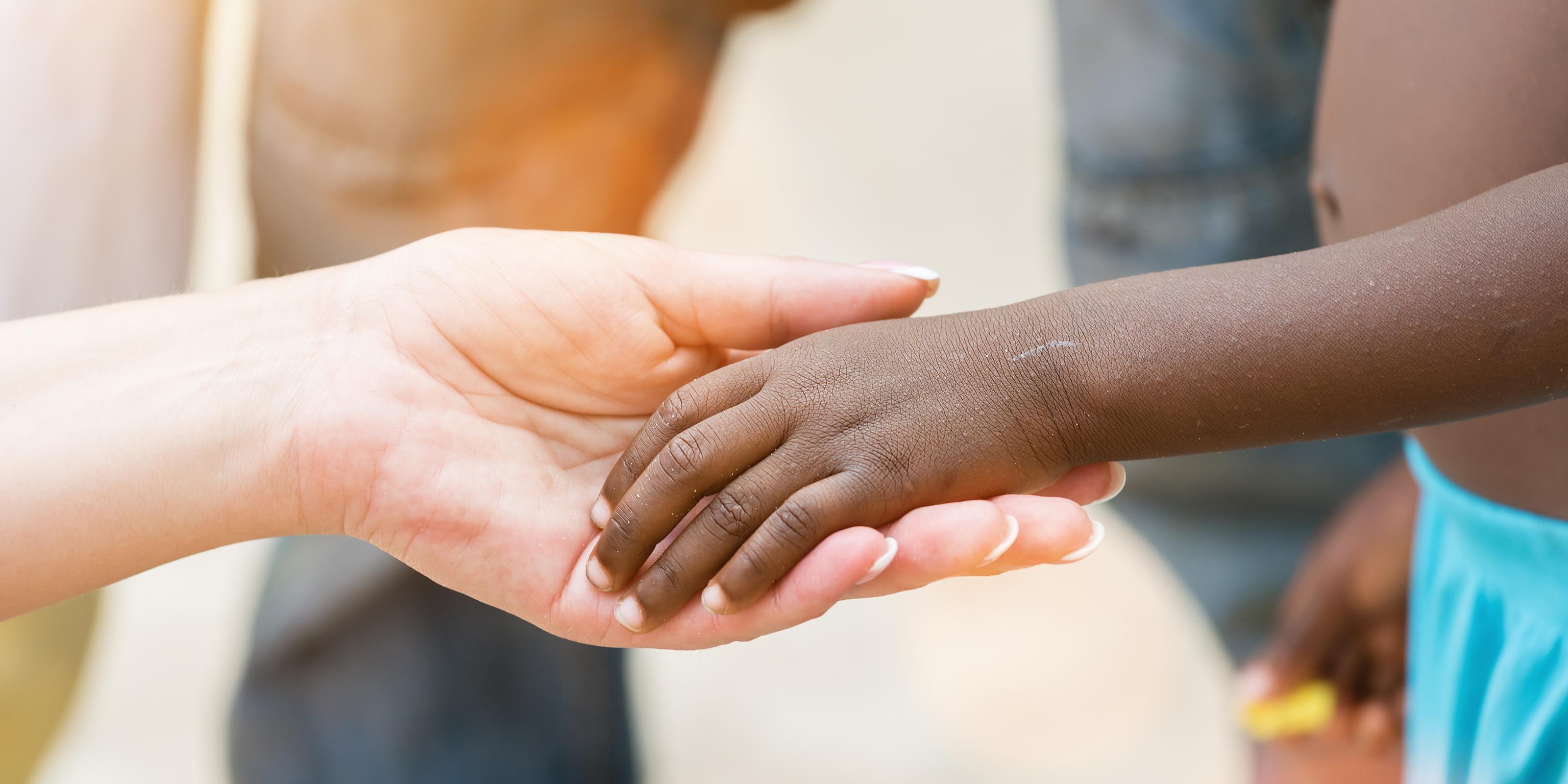 Kobieta trzyma za rękę ciemnoskóre dziecko