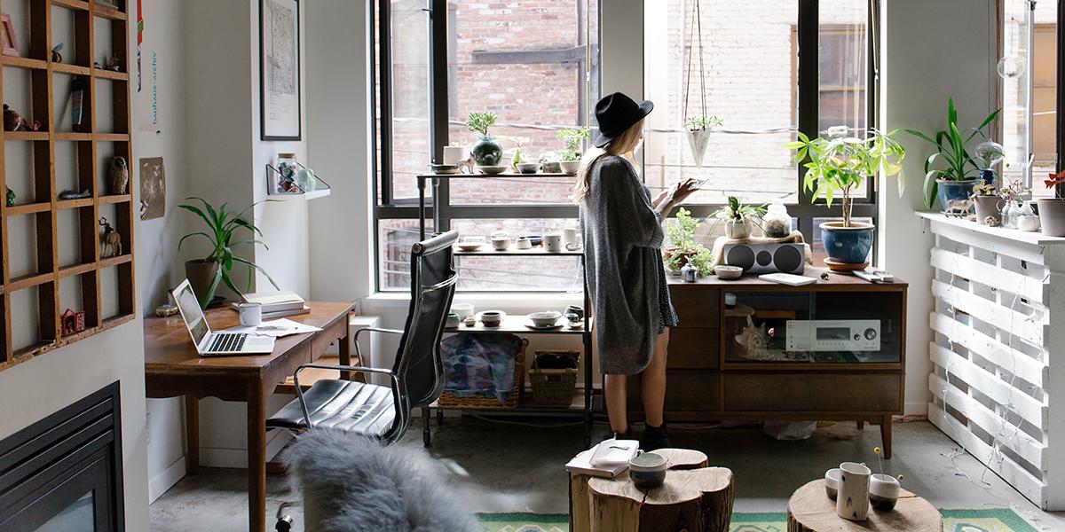 Dziewczyna w kapeluszu stoi w pokoju przy oknie