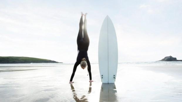 KOBIETA Z DESKĄ SURFINGOWĄ