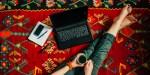 Nogi dziewczyny leżącej na dywanie z laptopem