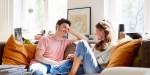 Uśmiechnięta para rozmawia ze sobą w domu na kanapie