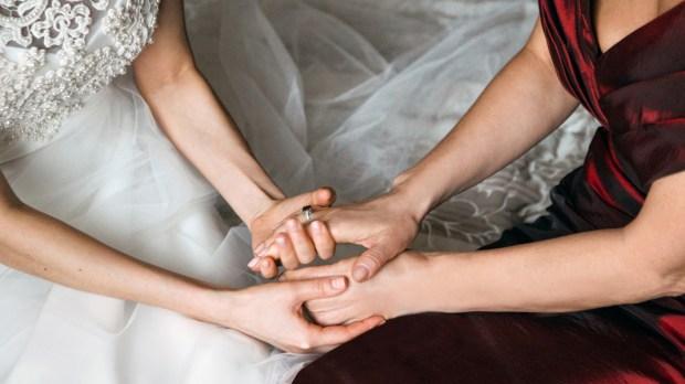 Panna młoda trzyma za ręce starszą od siebie kobietę