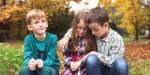 Trójka małych dzieci siedząca razem w parku