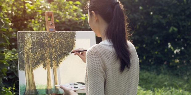 Artystka maluje obraz na zewnątrz