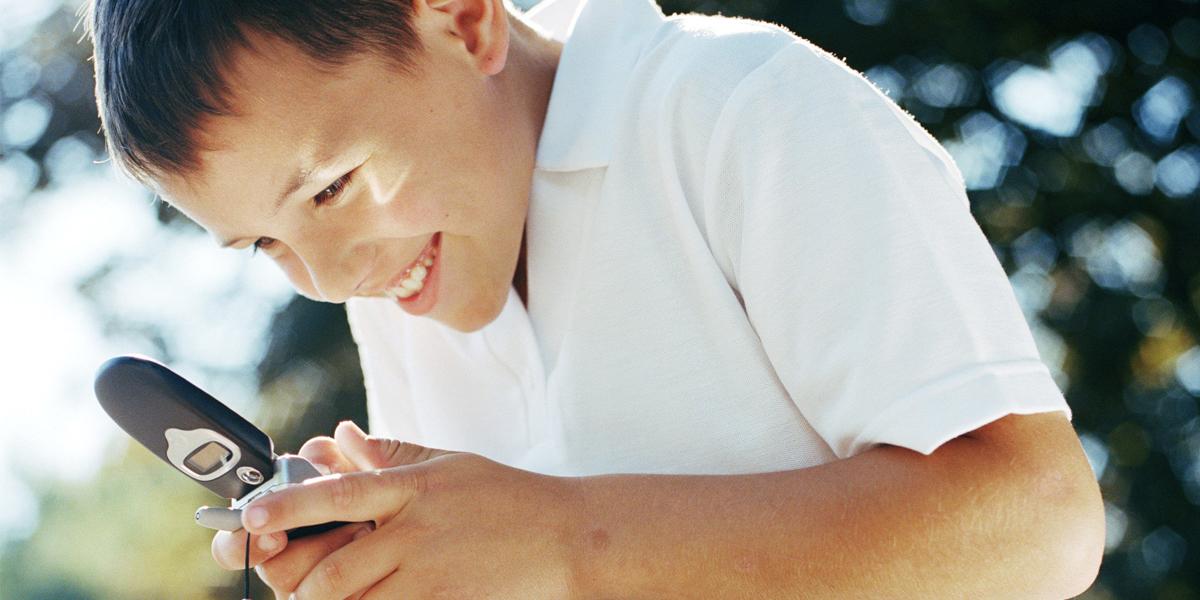 Uśmiechnięty chłopiec siedzi na ławce i bawi się telefonem komórkowym