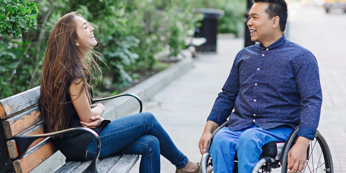 Dziewczyna rozmawia z chłopcem na wózku