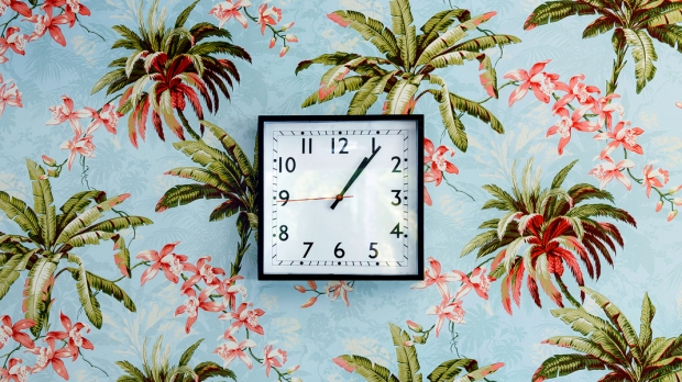 Kwadratowy zegar na ścianie pokrytej dekoracyjną tapetą