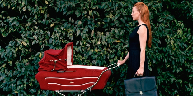 Bizneswoman idąca z teczką pcha przed sobą wózek z dzieckiem