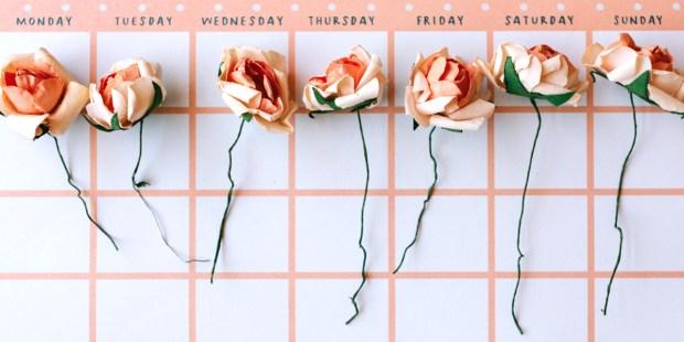 Sztuczne róże leżące na kalendarzu