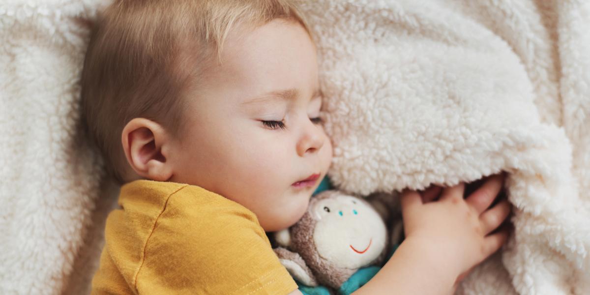 Śpiące dziecko przytulone do maskotki