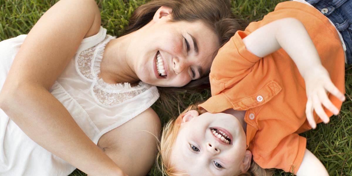 Młoda mama bawi się z synkiem na trawie