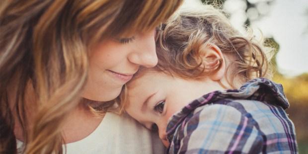 Mama z przytulonym dzieckiem na ramieniu