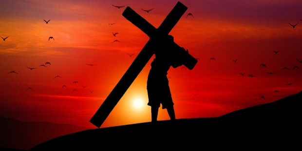Jezus dźwigający krzyż na tle zachodzącego słońca
