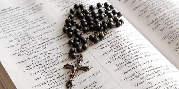 Czarny różaniec na tle Pisma Świętego
