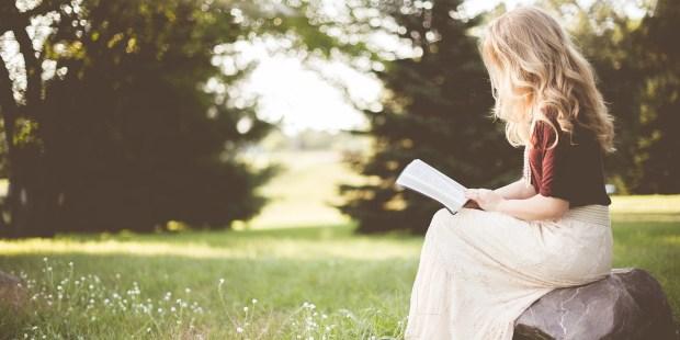 Kobieta siedząca w ogrodzie czyta Pismo Święte