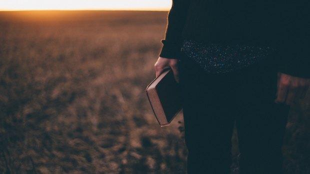 biblia-trzymana-w-reku zachod slonca