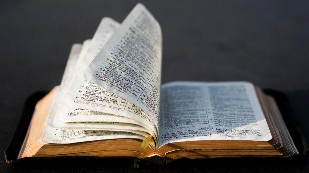 Otwarta Biblia ktorej kartki przewraca wiatr