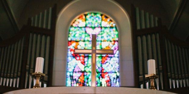 Krucyfiks na ołtarzu na tle witraża