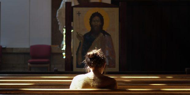 Dziewczyna modlaca sie przed ikona