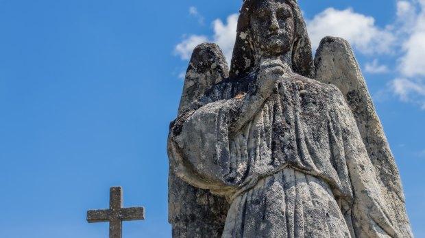 Kamienny aniol z krzyzem w tle