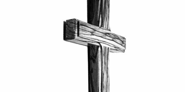 Drewniany krzyż na białej ścianie