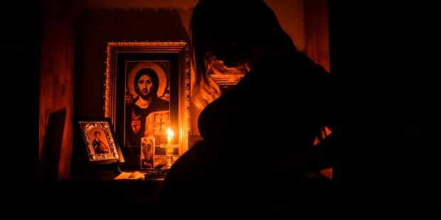 Modlitwa w polmroku przy ikonie