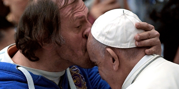 Pope Francis is kissed by a person