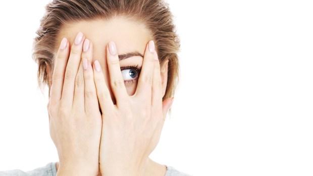 Obraz przerażonej kobiety zakrywającej oczy na białym tle